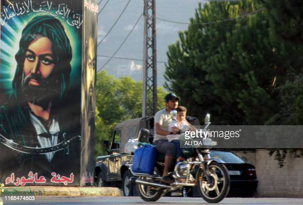 Men ride on a motorcycle past a large banner showing a picture of the late Shiite Muslim Imam Hussein ibn Ali put up ahead of the Shiite Muslim...