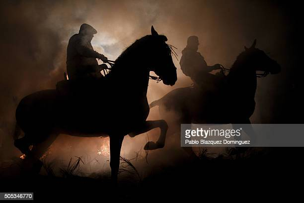Men ride on horses through the smoke of a bonfire during 'Las Luminarias' Festival on January 16 2016 in San Bartolome de Pinares Spain In honor of...