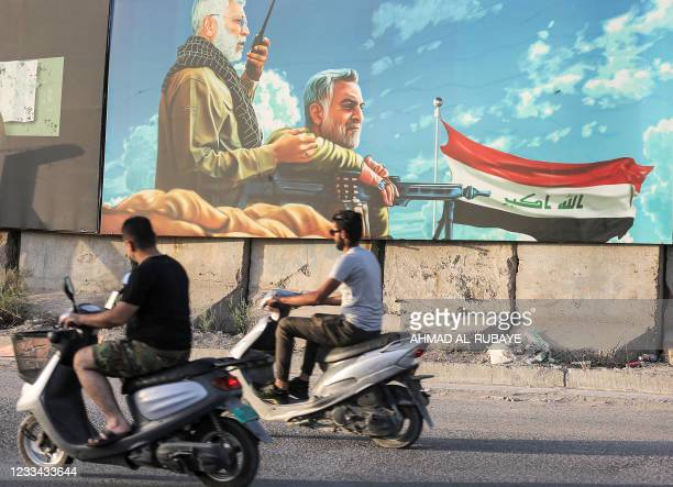 Men ride scooters past a billboard depicting the late commander of the Iranian-backed Hashed al-Shaabi paramilitary forces Abu Mahdi al-Muhandis and...