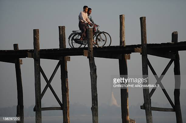 Men ride their bicycles on the U Bein's bridge as they cross the Taungthaman lake in Amarapura Myanmar's penultimate royal capital located 10 kms...