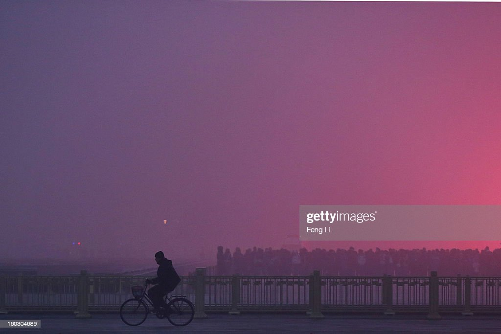 A men rides a bicycle as tourists waiting the flag-raising ceremony during severe pollution at Tiananmen Square on January 29, 2013 in Beijing, China. The 4th dense fog envelops Beijing with pollution at hazardous levels in January.