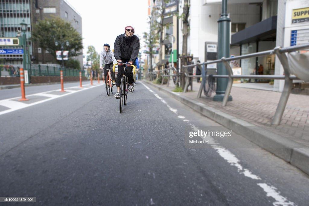 Men riding bicycles on street : Stock Photo