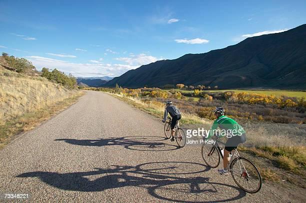 men riding bicycles through countryside, rear view - コロラド州 ニューキャッスル ストックフォトと画像