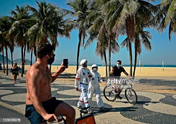 Men riding bikes take pictures of Brazilian accountant Tercio Galdino and his wife Alicea who walk along Copacabana beach wearing protective suits,...