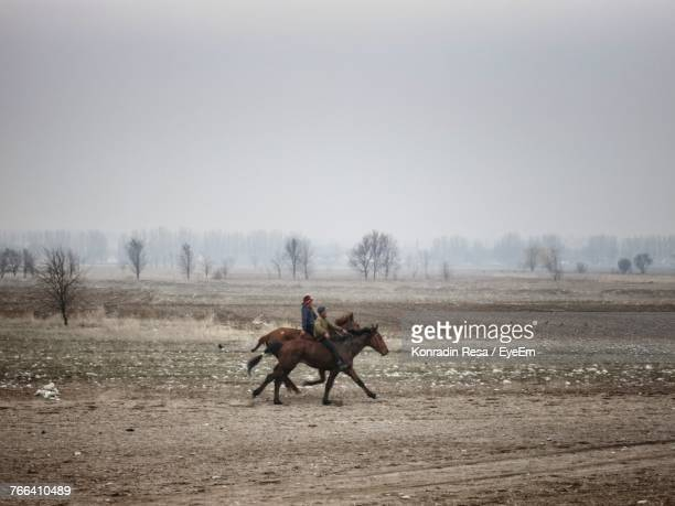 men riding horse on field against clear sky - キルギス ストックフォトと画像