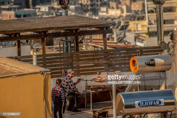 A men roasts a lamb on the roof of the house during the Orthodox Easter in Athens on April 19 during the COVID19 outbreak caused by the spread of the...