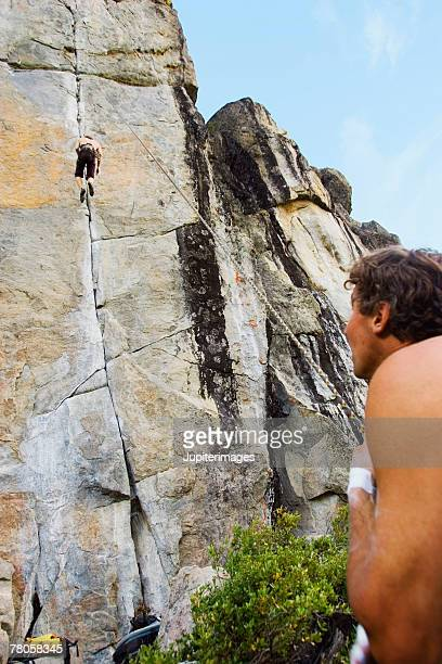 men rock climbing - rock overhang stock pictures, royalty-free photos & images