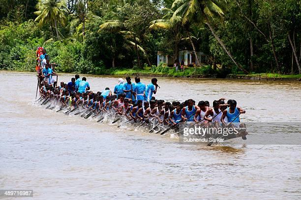 Men row a snake boat during Paipad Boat race