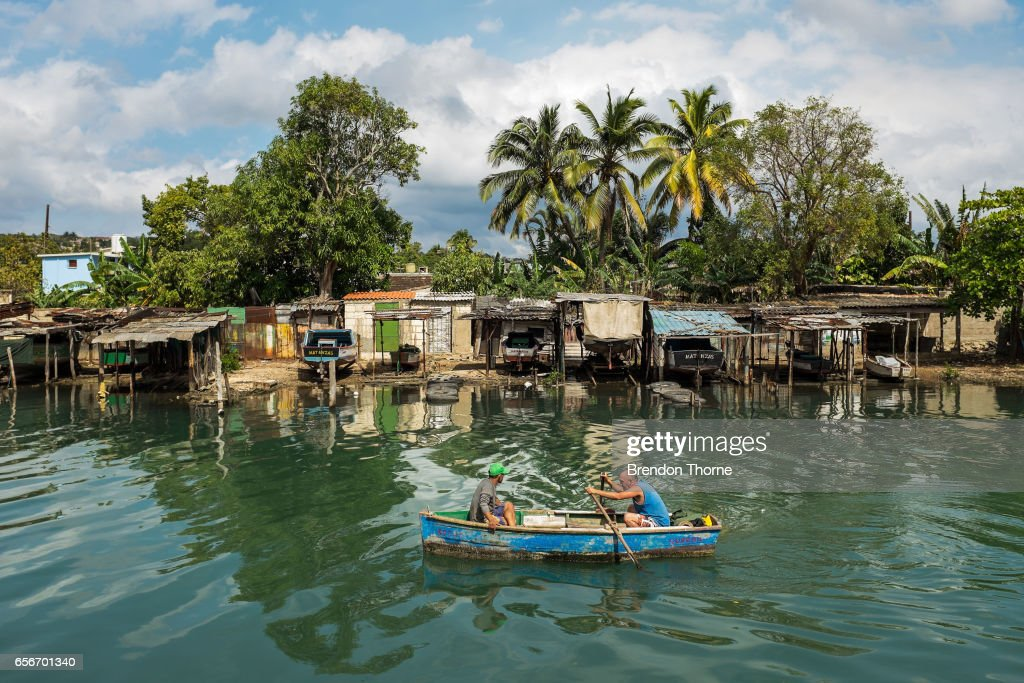 Men row an old boat along a canal on February 2, 2017 in Matanzas, Cuba.