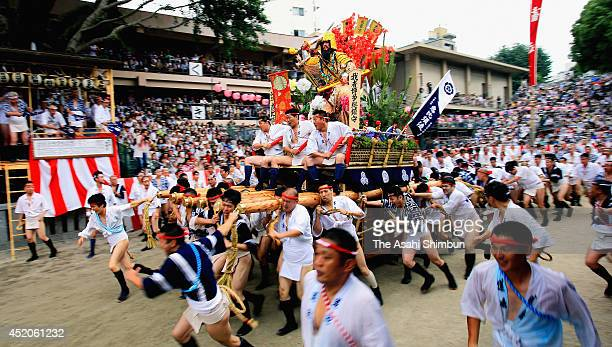 Men run carrying a float during the 'Oiyama Narashi' as a part of the Hakata Gion Yamakasa Festival on July 12 2014 in Fukuoka Japan The event is...