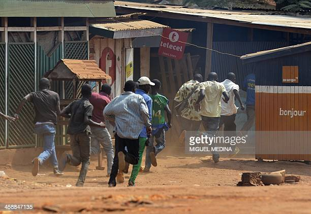 Men run during a protest against the French Sangaris intervention in the Galabadia neighbourhood close to the Centrafrican President's private house...