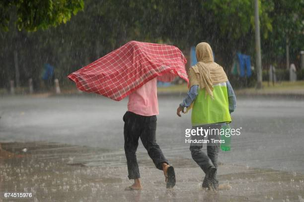 Men run for cover during a sudden downpour near India Gate on April 28 2017 in New Delhi India