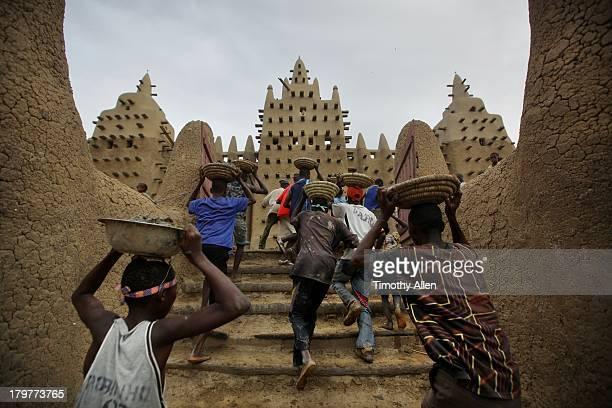 Men run up Great Mosque steps, Djenne
