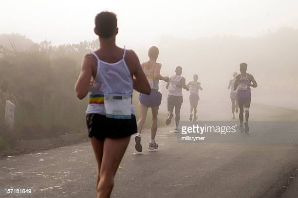 Men running in a mist while trying to win
