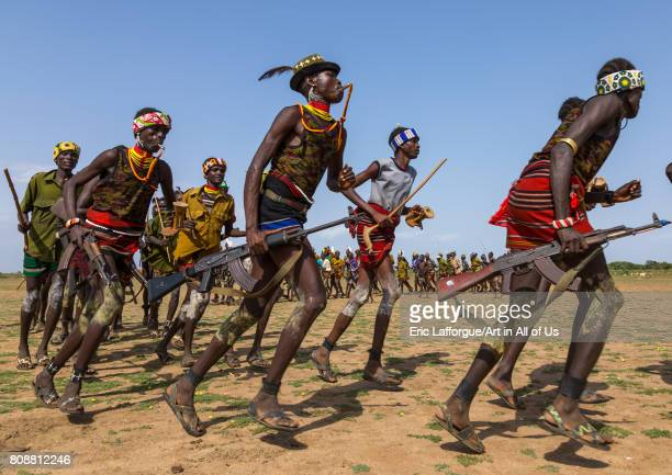 Men running in line with weapons during the proud ox ceremony in the Dassanech tribe Turkana County Omorate Ethiopia on June 6 2017 in Omorate...