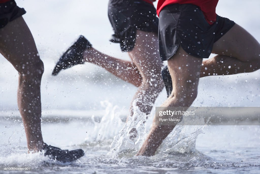 Men running in ocean, low section : Stock Photo