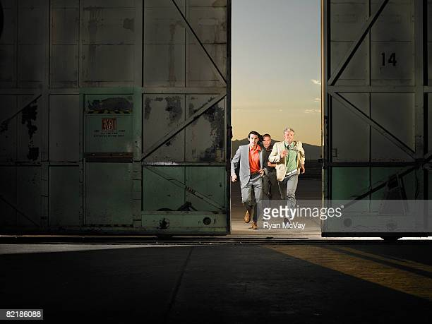 3 men running into  empty warehouse