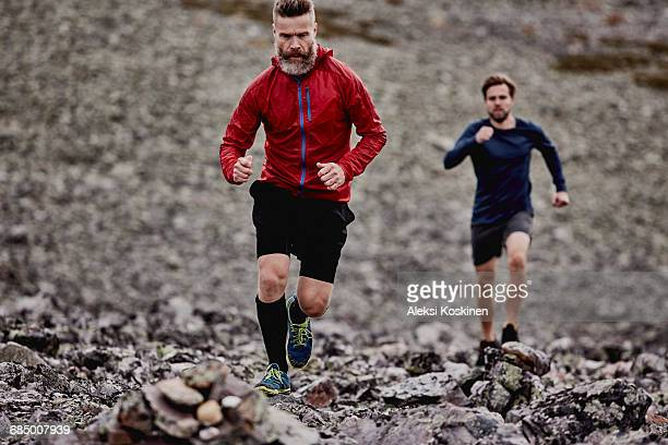 Men running on rocky cliff top, Kesankitunturi, Lapland, Finland