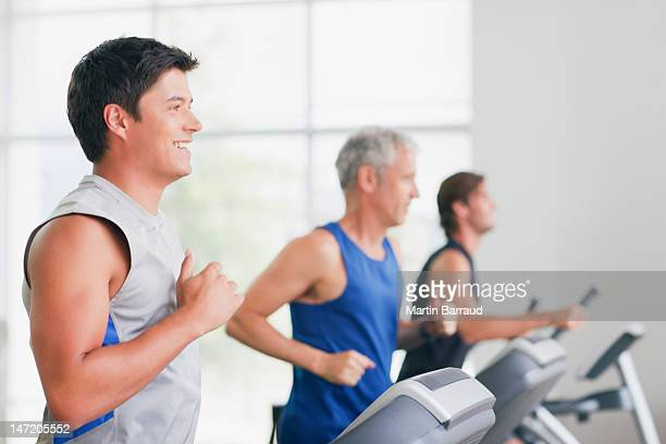Men running on treadmills in gymnasium