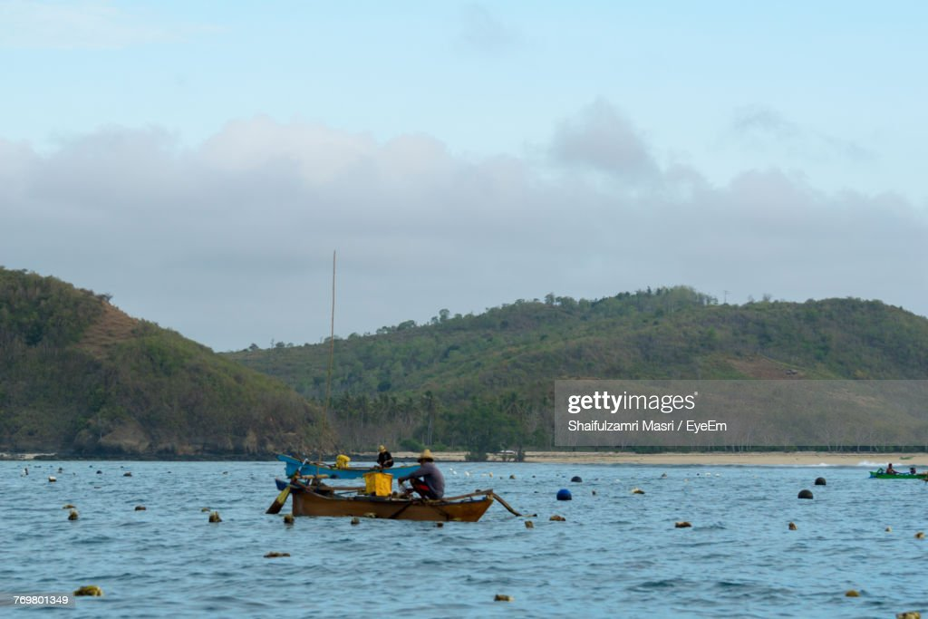 Men Sailing Boats On Sea Against Mountains : Stock Photo