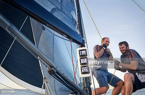 Men sailing pulling rigging equipment on sailboat