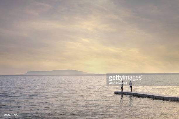 2 men sea fishing off dock