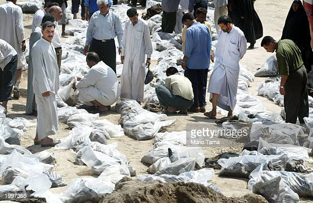 Men search through victims remains at a mass grave on May 14 2003 in Hillah Iraq At least 2000 bodies have been dug out at the site making it the...