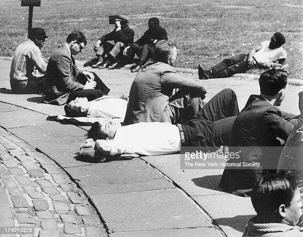 Men seated and lying in the sun Bryant Park New York New York April 15 1963