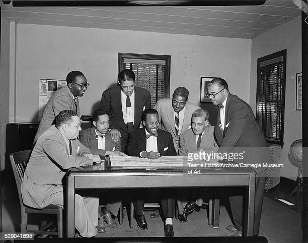 W Clyde Page Russell Washington Erroll B Davis Earl V Hord standing James Drake Mal Goode John B Johnson and Frank Lavelle posed around table looking...