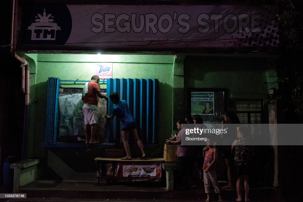 Men secure the window of a store ahead of Typhoon Mangkhut's arrival in Tuguegarao, Cagayan province, the Philippines, on Friday, Sept. 14, 2018. Super Typhoon Mangkhut is expected to threaten Chinas Guangdong coastline, and Hong Kong, with a possible direct strike that may cause as much as $120 billion in damage and economic losses. Photographer: Carlo Gabuco/Bloomberg via Getty Images