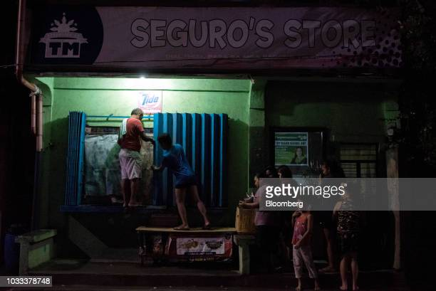 Men secure the window of a store ahead of Typhoon Mangkhut's arrival in Tuguegarao Cagayan province the Philippines on Friday Sept 14 2018 Super...