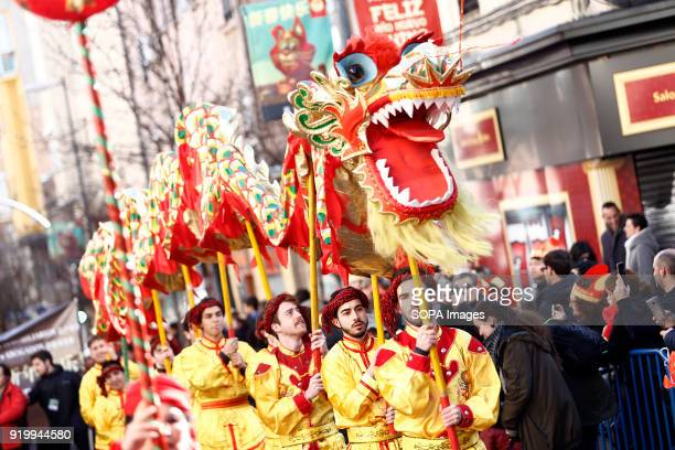 Men seen holding a huge dragon costume during the chinese new year parade Thousand of participants take part in the Chinese New Year parade in Madrid...