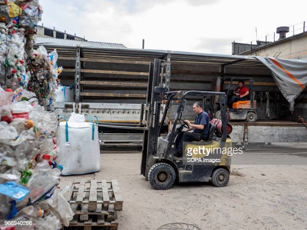Men seen operating a forklift and loading big bags with crushed plastic bottles into the truck to be sent for further processing In Ukraine...