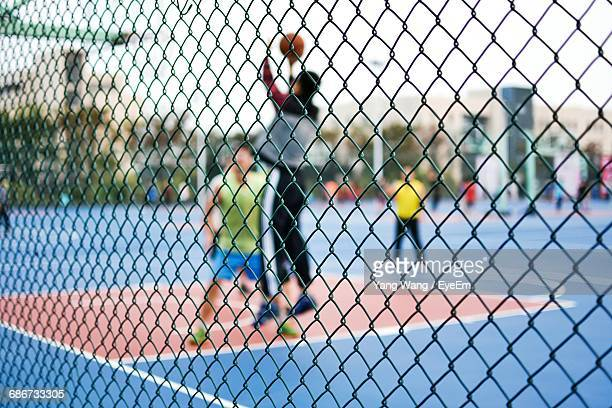 Men Seen Through Chainlink Fence Against Sky