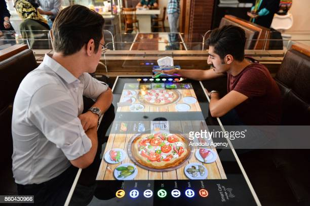 Men select their food served by robot waiter which moves on rail system placed between tables at the first robotic restaurant 'RoboChef' in Tehran...