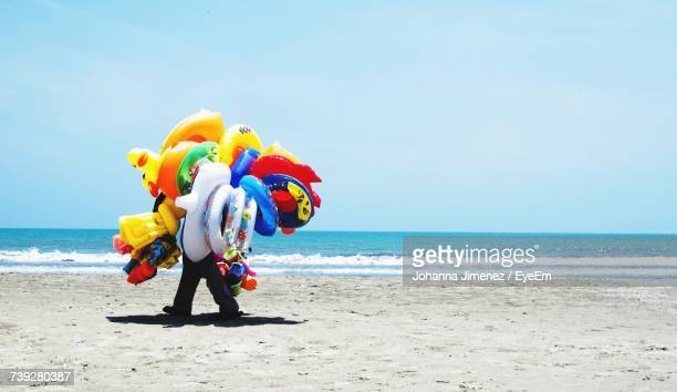 Men Selling Balloons On Beach Against Clear Sky