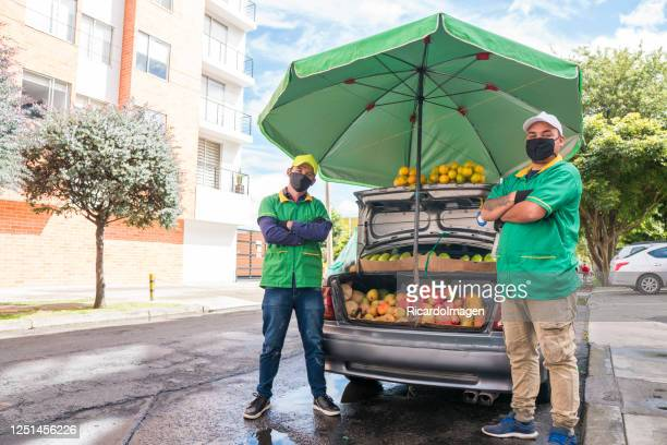 men selling fruits and vegetables in a car while wearing face masks to protect themselves from the covid-19 virus - colombia stock pictures, royalty-free photos & images