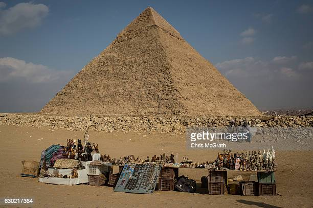 Men selling souvenirs at Egypt's famous Giza Pyramids wait for customers on December 18 2016 in Cairo Egypt Since the 2011 Arab Spring and continued...