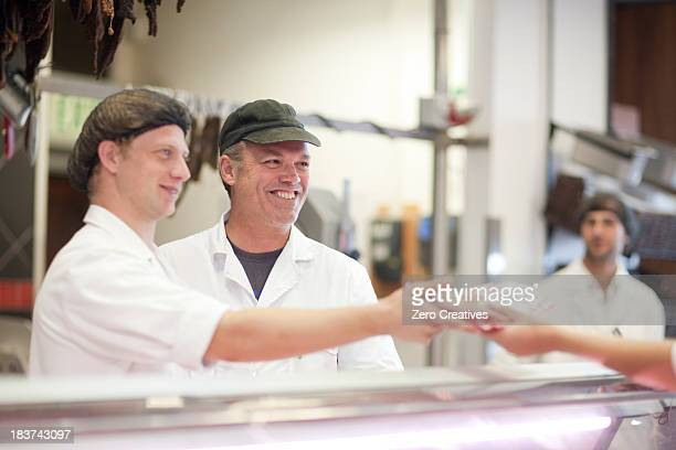 men serving customer on butcher's counter - butcher's shop stock pictures, royalty-free photos & images