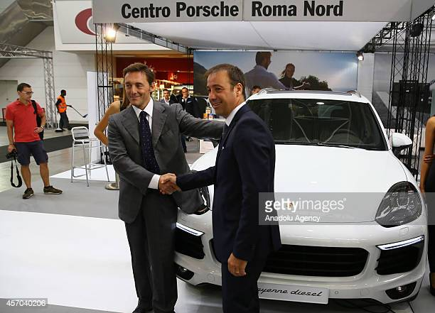 Men shake hands in front of a Porche Cayenne Diesel presented during the Supercar Roma Auto Show in Rome capital city of Italy on October 10 2014