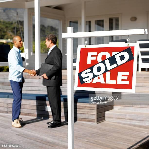 men shaking hands behind a sold signboard