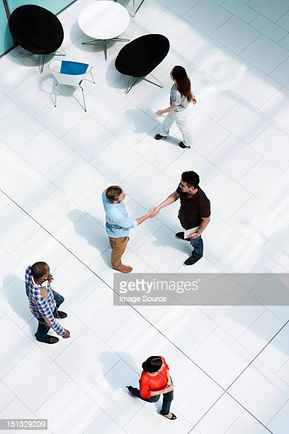 Men shaking hands on concourse