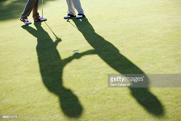 Hommes se serrant la main sur un putting green