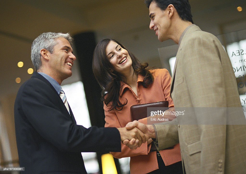 Men shaking hands, woman behind them. : Stockfoto