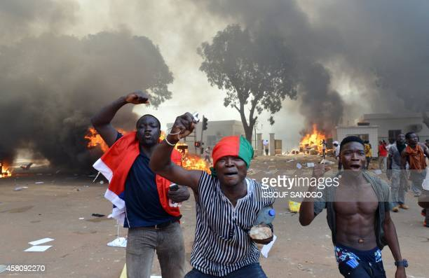 Men shout slogans in front of burning cars near the Burkina Faso's Parliament where demonstrators set fire on October 30 2014 in Ouagadougou as they...