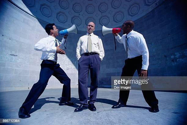 Men Shouting at Businessman with Bullhorns
