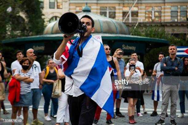 Men shouts for a parlarte to ask for help from Cuban protesters in Union Square Park on July 14, 2021 in New York City. A small group of people...
