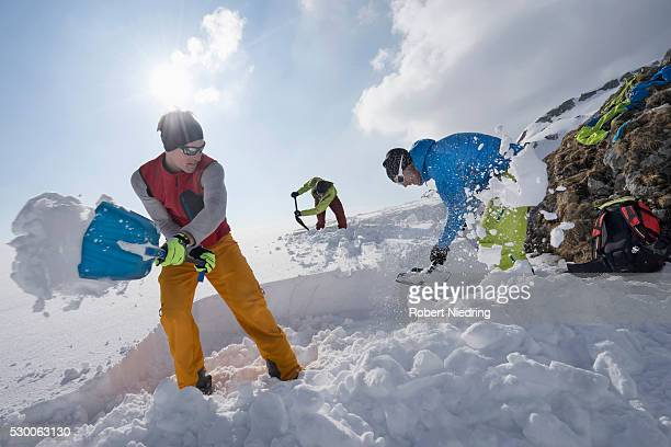 men shovelling snow for bivouac camp, tyrol, austria - snow shovel stock photos and pictures