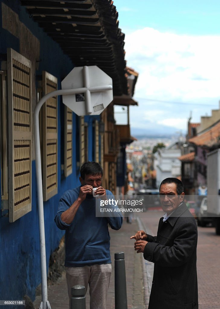 Men sip on coffee at a street corner in the historic neighborhood of La Candelaria in Bogota on September 17, 2009. La Candelaria is Bogota's oldest neighbourhood and the city's historical center, known for its colonial houses with wooden balconies and clay shingle roofs. AFP PHOTO/Eitan Abramovich -------------- MORE