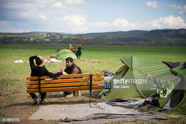 Men sit and chat on a bench they have placed besides their tent at the Idomeni refugee camp on the Greek Macedonia border on March 11 2016 in Idomeni...